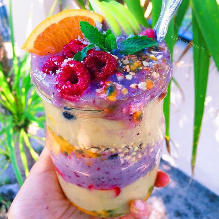 A thick mango mixed berry smoothie layered together with