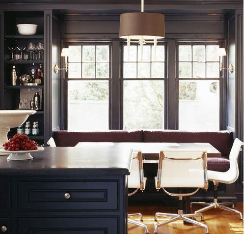Breakfast nook with banquette seating and Eames Aluminum side chairs. Love the charcoal/navy wall color too. Designed by Colleen McGill.