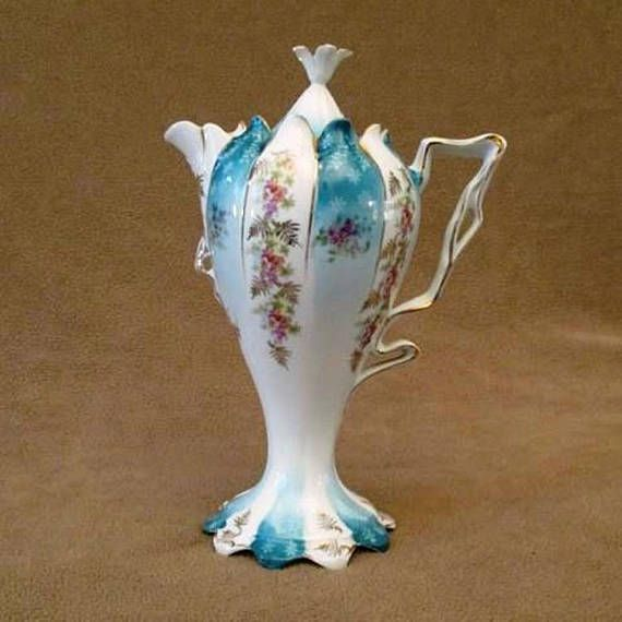 Antique R S Prussia Pedestal Chocolate Pot is beautifully decorated with bright flowers, a ribbon handle, and is trimmed with gold.