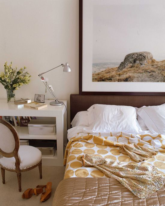 oversized framed photograph art takes the place of a headboard like the idea of small nightstandbookshelf as desk next to bed maximize space usage