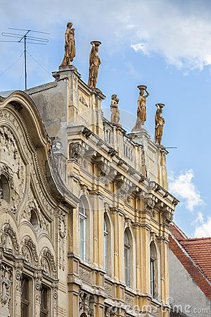 Old classic architecture building with statues on the frontispiece in historical center of Brasov city, Romania.