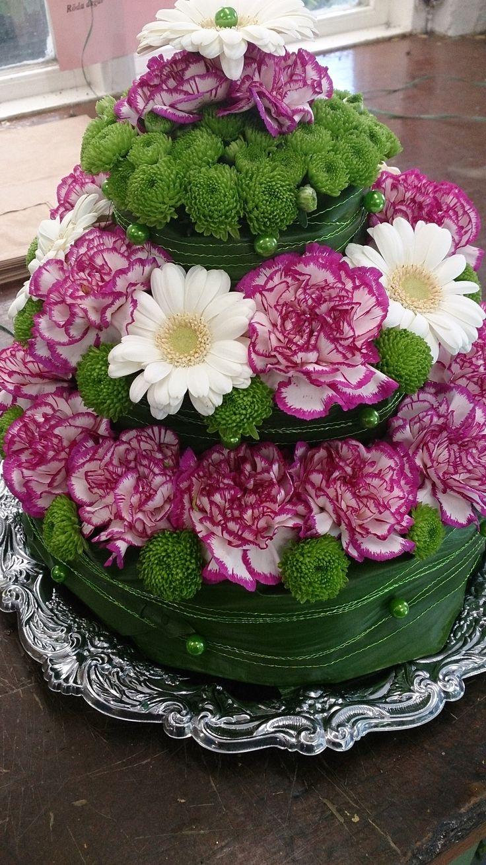 Denna häftiga blomstertårta har vi fått in som Dagens Blommogram från Konga Handelsträdgård i Konga. Den var till avtackning av en man som skulle gå i pension. Vet inte om mannen var väldig förtjust i tårta, men det blev en trevåningstårta av nejlikor, santini, germini, aspedistrablad och såklart lite garnering .  Blommor, interflora