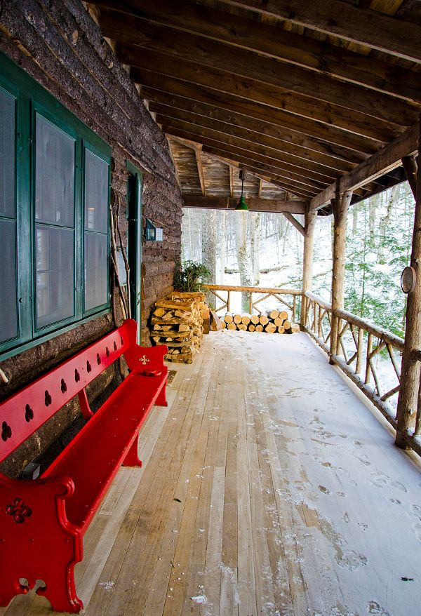 A dusting of snow on this rustic log porch with what appears to be a red painted church pew bench.