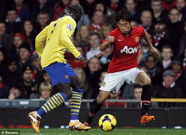 Shinji Kagawa attempts to dribble past Bacary Sagna