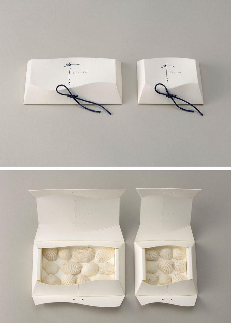 パッケージ 江戸時代から伝わる精巧な貝の木型から生まれた和菓子。伝統的食文化を現代に伝える恋文のような和菓子を表す「かしこ」というネーミング。讃岐和三盆を使用し、販売は直島のベネッセ・アートサイト。それらにふさわしい顔つきを考えた結果、ゆるやかな波を象ったパッケージが誕生しました。 Japanese Shell-shaped Wagashi Packaging