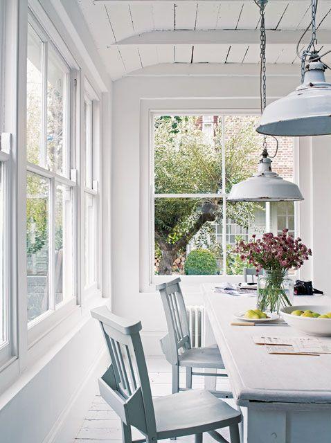 Cocina rústica en blanco con ventanas al jardín, parte de la maravillosa casa del fotógrafo Paul Massey en Parsons Green, Londres. Fotos gentileza Paul Massey