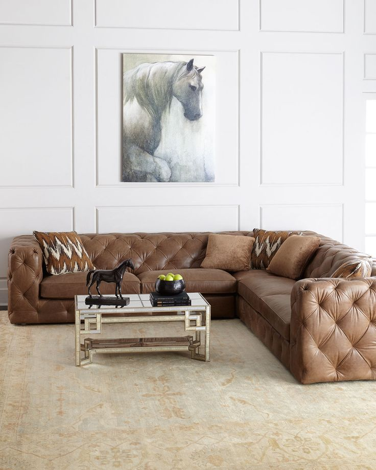 tufted leather sectional with square arms. traditional paneling in neutral room.