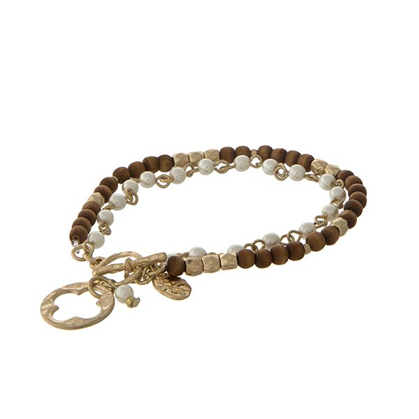 "Brown wood bead and faux ivory pearl toggle bracelet with a gold tone quatrefoil charm. Approximately 7"" in length. 
