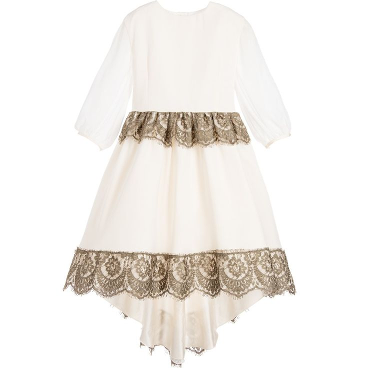 Girls luxurious, handmade ivory dress by Aristocrat Kids. Made from a layer of beautiful silk georgette, with sheer sleeves and fabric covered button fastenings. It has a fitted bodice, a full and voluminous skirt, with an under-layer of silk taffeta and tulle frills attached to the smooth cotton lining. It has a bronze lace trimmed waist with a sash to tie at the back. The elegant shaped hem is longer at the back with a matching lace trim. Super for bridesmaids and other special occasions. …