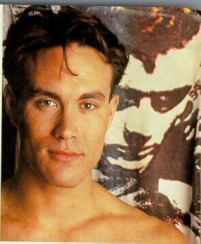 Brandon Lee and a photo of James Dean in the background