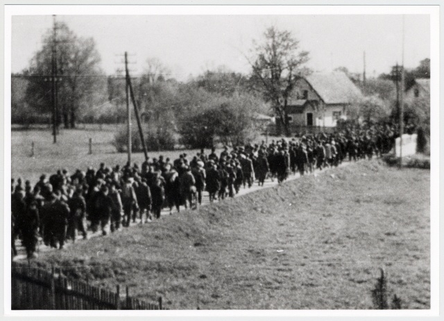 Clandestine photograph of prisoners marching to Dachau. Maria Seidenberger took the photo from the second story window of her family's home while her mother stood outside and gave potatoes to the prisoners. Both actions were done at extreme risk.  Maria's photos documented the death march and atrocities committed by the Nazis.  In addition, she hid photos and correspondence made by inmates at Dachau, all at great peril to her life.  She and her mother both survived the war.
