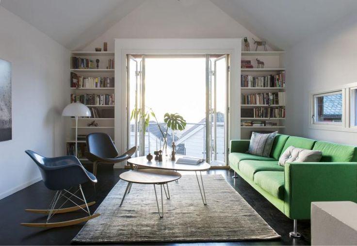 SMAL OG HØY STUE: Rommet henvender seg mot balkongen i sør – mot lyset, og utsikten. Park Sofa og Eames Plastic Armchair fra Vitra. Sofabord, teppe og Shell Chair fra Verket interiør. Bokhyllene på hver side av foldedørene er tegnet av arkitekt Søren Sandved.