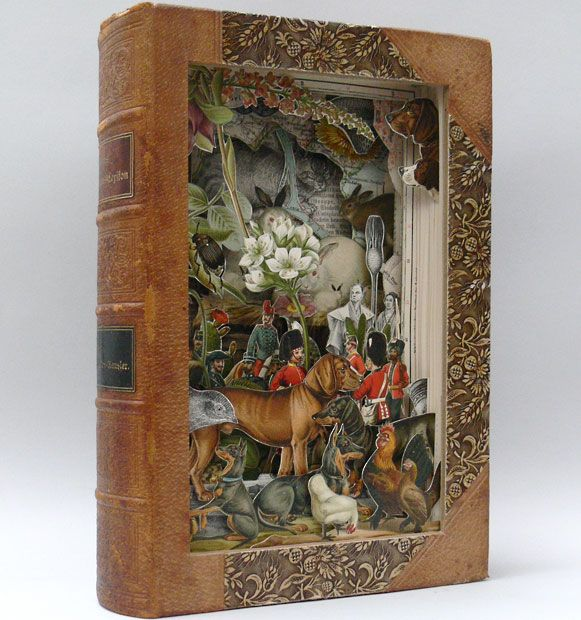 """Canis,"" book paper sculpture by Alexander Korzer-Robinson.  ""My creations have been made by cutting into the book, cutting around some of the illustrations and removing others.  The composition is built using only the imagery that is already in a particular volume.  The end result is a hollowed out book with layered composition that is like the Victorian paper theatres."""