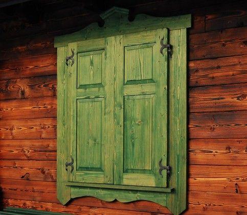 Zielone okiennice domu z bali