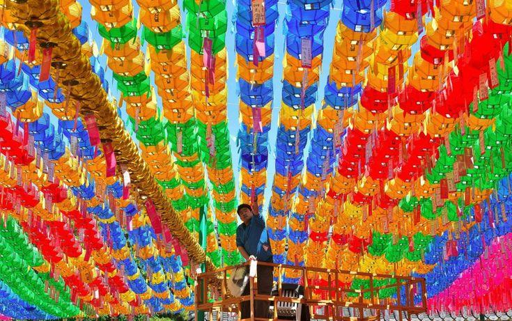 Una mujer enciende una vela en la ermita de El Rocío, Un vendedor de globos busca clientes en Colombo... Te mostramos las mejores fotos de la jornada