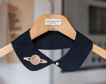 Cotton Peter Pan collar featuring golden sequin planet patch on one side. With golden dome button