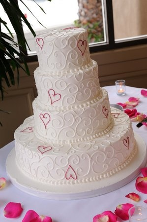 Having a heart themed wedding? If so, this 4-tier, scrolled wedding cake featuring red or hot pink hearts is perfect.