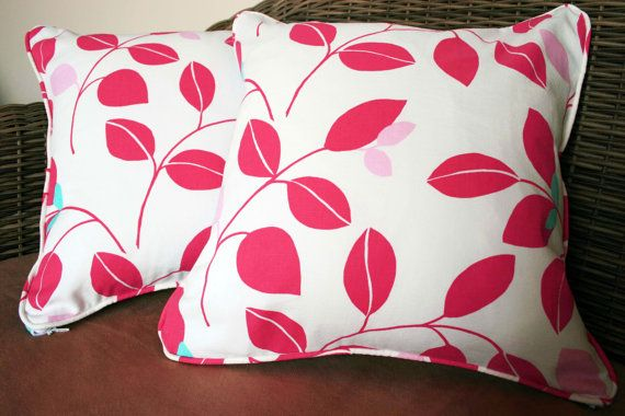 These 16 leaf print cushion covers come as a pair. The fronts have a fuchsia and aqua blue leaf pattern, while the back is a plain aqua satin