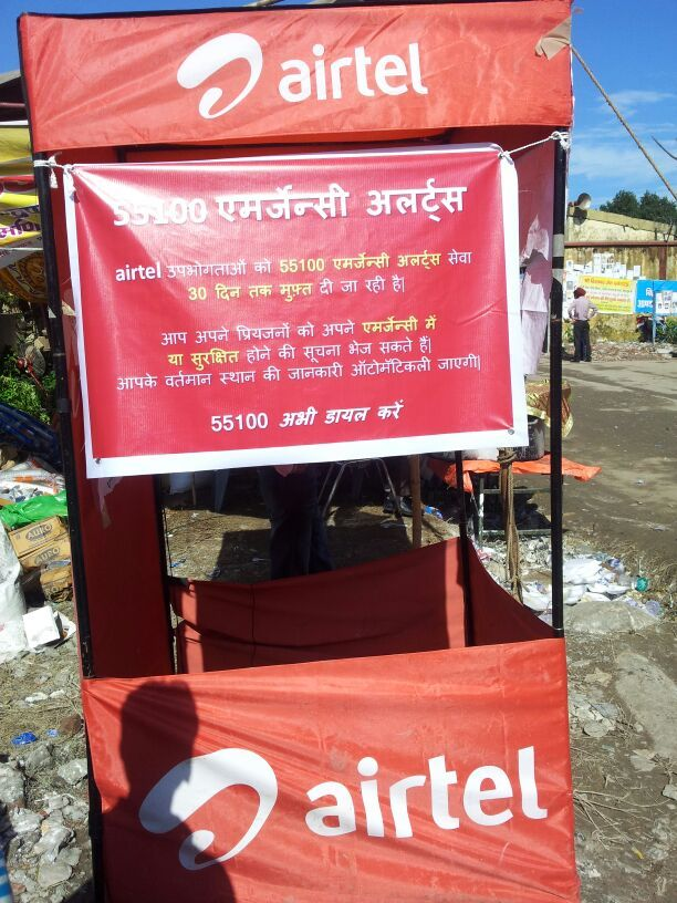 55100 Emergency Alerts banner displayed at Airtel booth in the relief camp.