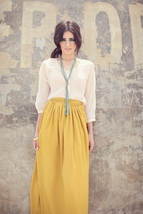 yellow skirt, cream blouse, blue necklace.  gorg.