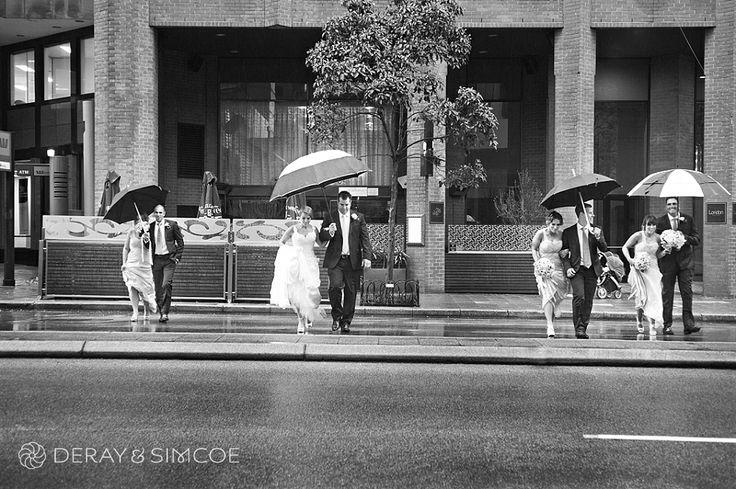 01 wedding party walking across st georges terrace raining umbrellas classic black and white timeless wedding photographer perth.jpg