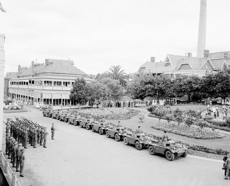 Crowds of people (including patients) watching a parade of nine Australian Army Ferret Scout cars and soldiers in the grounds of the Heidelberg (Repatriation) Hospital, 1954