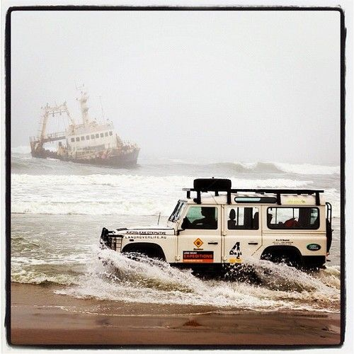 Land Rover Defender on a beach with a shipwreck