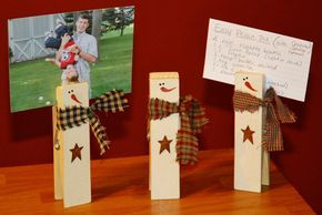 14. Snowmen Photo-holders from Giant Clothespins  It's really easy to make a couple of these photo-holders from giant clothespins. They're great for holding cards, pictures, or recipes around the holiday season.