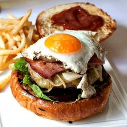 Aussie Burger with the lot - a sandwich filled with lettuce, tomato, beef patty, cheese, ketchup, beetroot, fried onions, bacon, pineapple and a fried egg on the top!