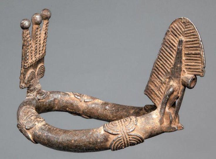 BELLE CHEVILLÈRE BWA en fonte d'aluminium avec sur l'avant la représentation du danseur Dwo porteur du masque de feuille. Burkina-Faso. Long.: 18 cm Reproduit page 63. -