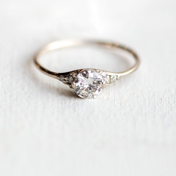 Featuring a stunning white center diamond surrounded by tiny white diamonds on either side, this antique-inspired engagement ring marries simplicity with sparkle in solid 14k yellow gold. A classic style to suit any era, this ring is designed to be a last