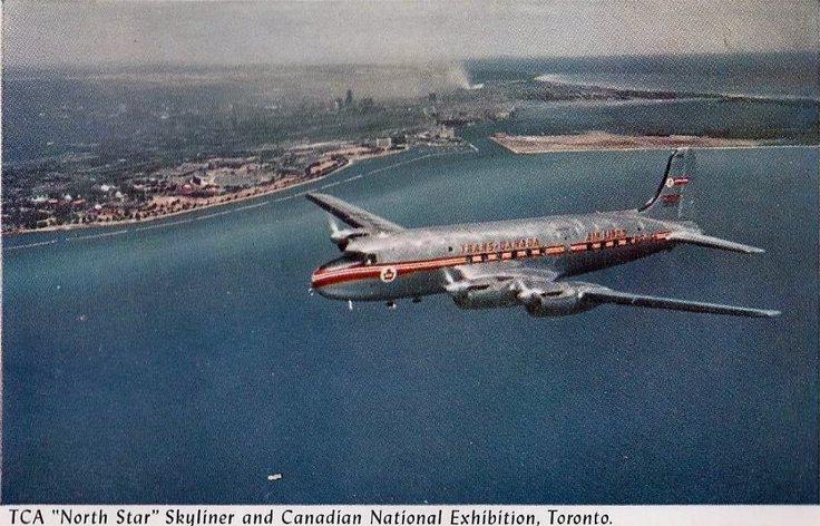 A Trans-Canada Airlines 36 passenger North Star Skyliner airplane flying above Lake Ontario with the CNE and downtown Toronto in the background, circa 1948.