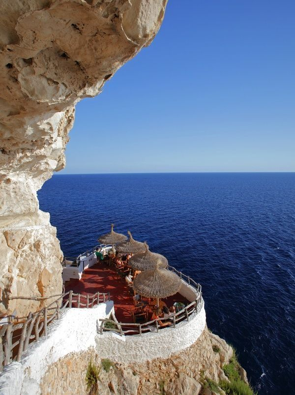 Seaside Cafe, Menorca, Spain - i've been here, the rest of the cafe is built into the cliff like a cave and becomes a nightclub in the evening.