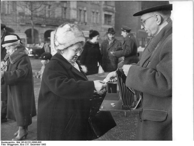 """31.12.1963 Berlin: Zahlreiche Westberliner kammen auch am Silvestertag 1963 in die Hauptstadt der DDR, um hier gemeinsam mit ihren Verwandten Neujahr zu feiern. UBz. Um den Geldumtausch an den Grenzkontrollpunkten zu beschleunigen, sind für die schnelle Abfertigung der Westberliner Gäste neben den Schaltern der Wechselstellen auch Angestellte der Deutschen Notenbank eingesetzt, die """"fliegende Geldwechselstellen"""" auf der Straße unterhalten. Hier nahe dem Grenzkontrollpunkt Chausseestraße."""""""