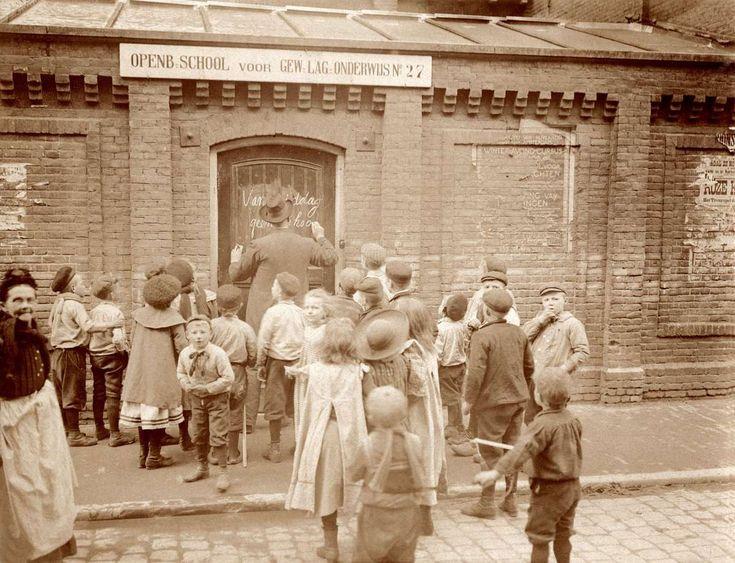 De Openbare School voor Gewoon Lager Onderwijs No. 27 blijft een middag gesloten in verband met de geboorte van kroonprinses Juliana: De hoofdonderwijzer schrijft in schoonschrift op de voordeur vanmiddag geen school,  [Grote Wittenburgerstraat 39 te Amsterdam], Nederland 30 april 1909.