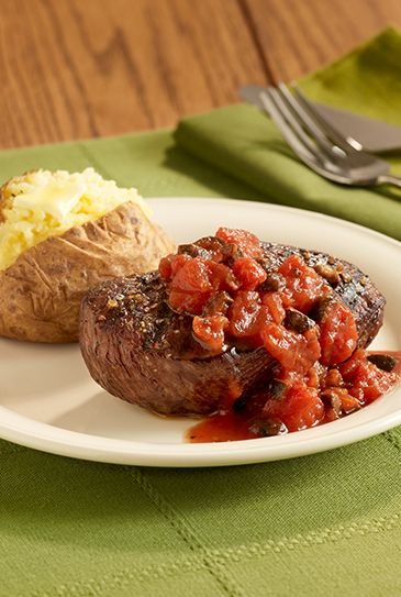 Juicy grilled steak recipe is topped with seasoned tomatoes and ripe olives for a simple main dish