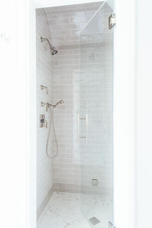 Small walk in shower features gray subway tiles on ceiling and walls lined with a hand held polished nickel shower kit over a white marble herringbone shower floor finished with a seamless glass shower door.