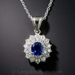 A delightful deep blue faceted oval sapphire, weighing 1.47 carats, is lavishly enshrined in a double halo composed of bright white and sparkling round brilliant-cut diamonds, totaling .96 carat, in this classic estate drop necklace crafted in gleaming platinum. Just shy of 1 inch with loop, 18 inch platinum chain.