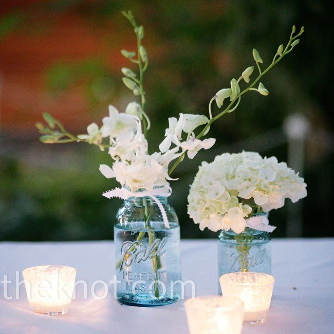 Blue ball jars filled with white hydrangeas and orchids