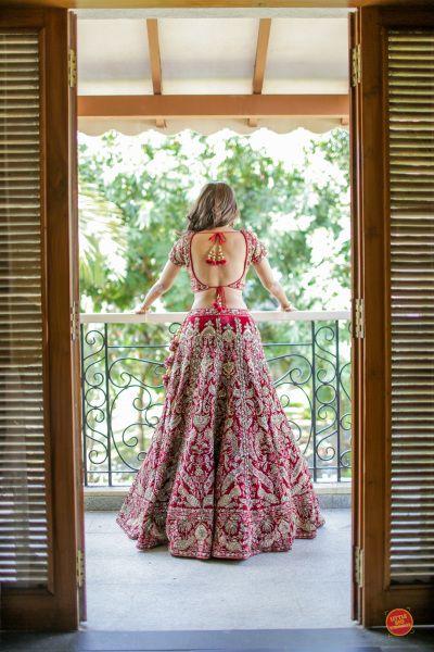 Bridal Lehengas - Bride in a Red Lehenga with Golden Embroidery | WedMeGood | Photo by: Little Big Weddings #wedmegood #indianbride #indianwedding #bridal #weddinglehenga #lehenga #backlessblouse