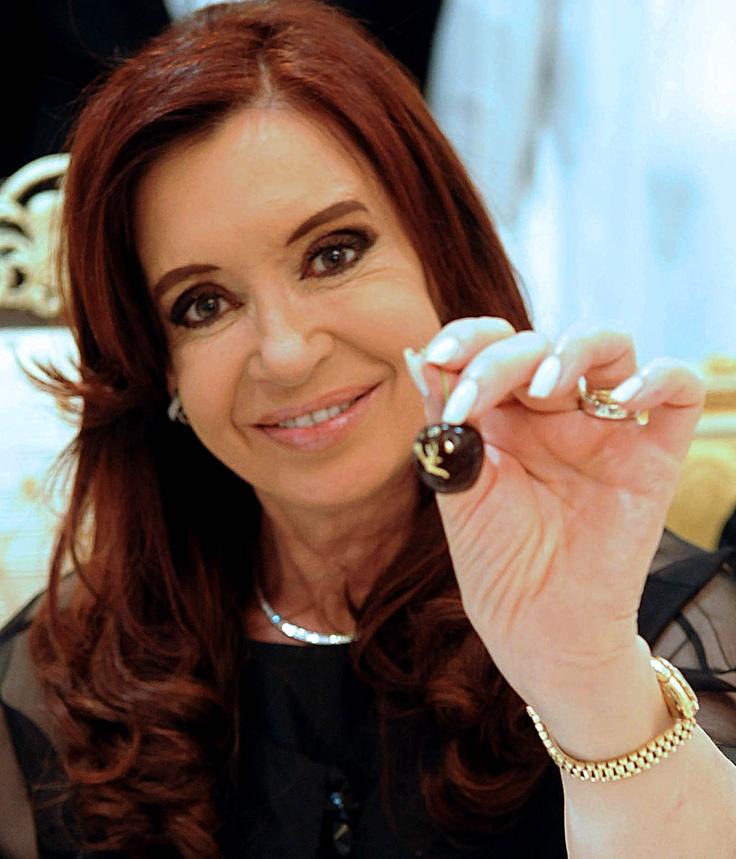 Cristina Fernandez de Kirchner exhibe una cereza patagónica como las que Argentina exporta a los Emiratos Árabes Unidos, en su visita oficial a esa federación arábiga.