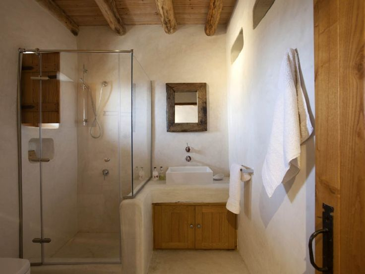 #reforma #baño rústico en casa rural con lavabo sobre mueble de obra, zona de ducha con cerramiento de vidrio y mampara.
