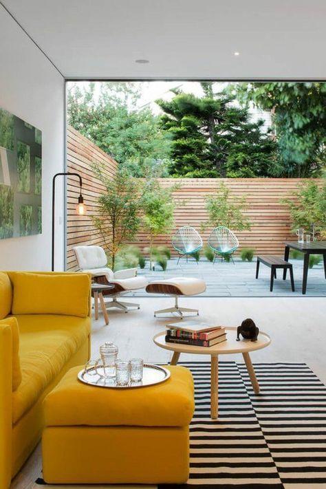 canapé jaune moutarde, tapi à rayures et petite table ronde en bois
