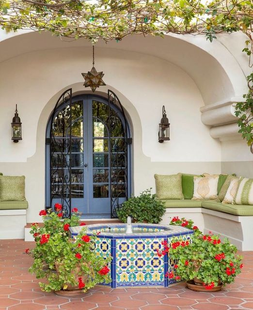 The rear exterior courtyard is enlivened by a seating niche with a pair of stucco banquettes covered with indoor/outdoor cushions and pillows behind a small Moroccan-style fountain with colorful tiles.