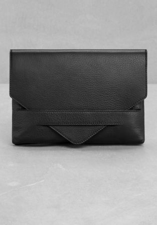 Made from soft natural grain leather, this pouch has a foldover flap that tucks into a stitched slit on the front.