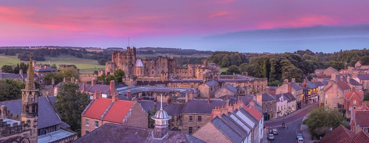 stayning in alnwick castle. View from Pottergate Tower across the historic rooftops of the town to Majestic Alnwick Castle and the Duke's Pastures beyond