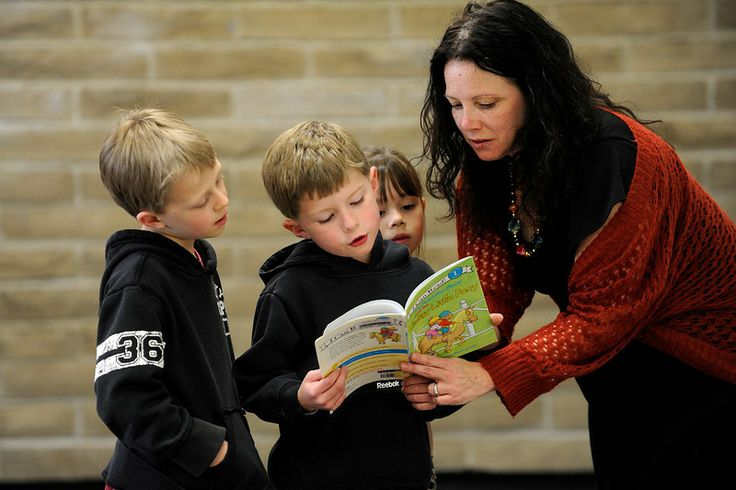 AURORA, CO - MARCH 18: Jamie Bauer, right, references a Berenstain Bears book with David DelaGarza, 6, Kaleb Cain, 6, far left, and Olivia C...