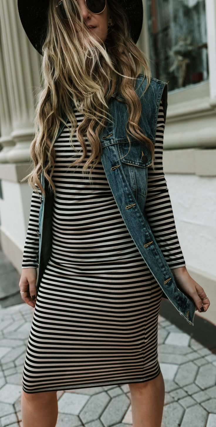 Edgy fall outfit styled with striped midi dress, oversized denim vest, and black fringe booties