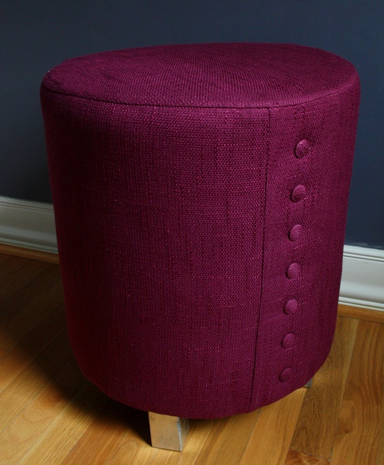 Ottoman with buttons on the side, could be storage of pillows, rolled duvet or something else roundish, wrapped up in the cover.