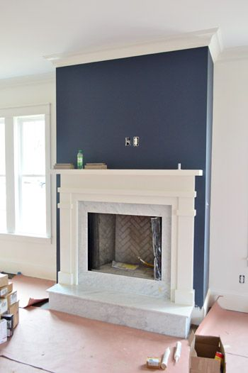 white walls with navy blue accent. white marble and herringbone tile gas fireplace with white mantle